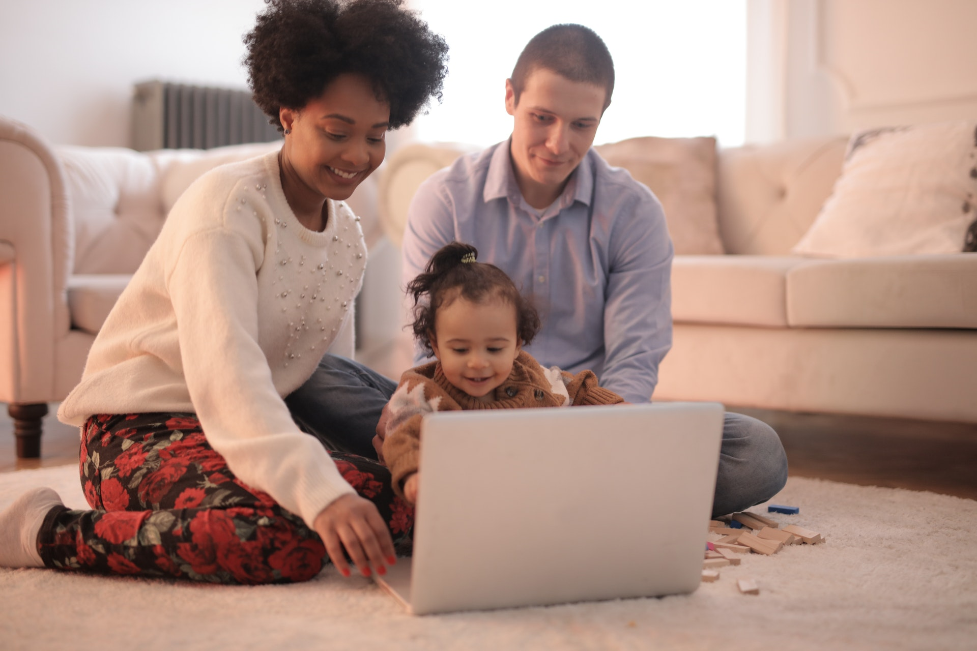 Photo of a family sitting on the floor using a laptop together